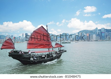 Junk boat with tourists in Hong Kong Victoria Harbour - stock photo