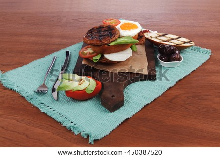 junk food big beef hamburger fried eggs on dark wood plate with modern cutlery ketchup sauce and pickels on blue mat isolated over white background - stock photo