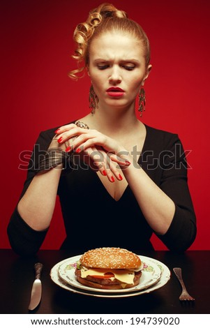 Junk food concept. Portrait of unhappy luxurious red-haired model in black cocktail dress trying to eat burger. Perfect hair, skin, make-up and manicure. Golden accessories. Studio shot - stock photo