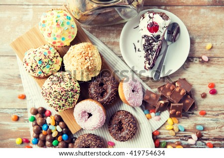 junk food, culinary, baking and eating concept - close up of glazed donuts, cakes and chocolate sweets on table - stock photo