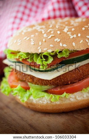 Junk food hamburger concept. Deep fried chicken or fish burger sandwich with lettuce, tomato, cheese and cucumber on wooden background. - stock photo