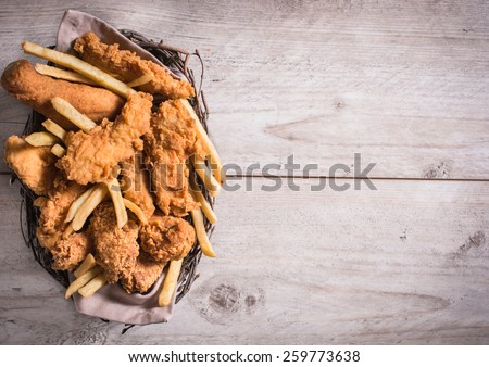 Junk food in the basket with blank space on the right side  - stock photo