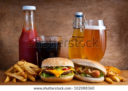 Junk food with burger, hotdog, french fries, cola, ketchup and beer on a wooden background - stock photo