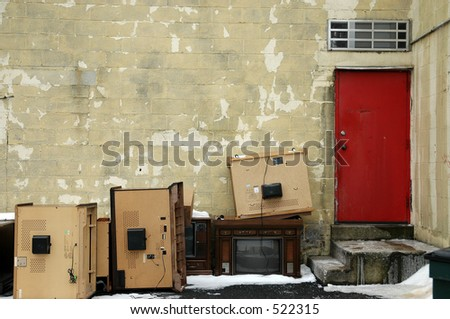 Junk TVs sitting outside a red door.