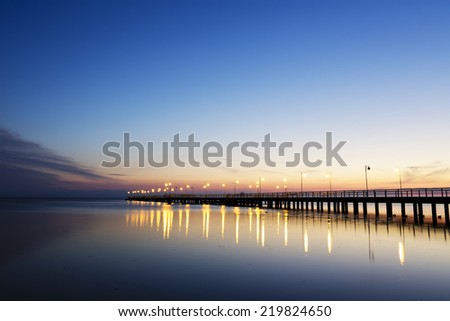JURATA, POLAND - SEPTEMBER 11, 2014: Night view of Wooden Pier with a length of 320 meters, built in the 70s of the 20th century, located at the Baltic Sea coast at the waters of the Gulf of Puck