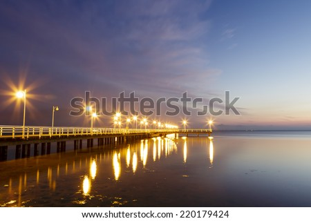 JURATA, POLAND - SEPTEMBER 11, 2014: Night view of Wooden Pier with a length of 320 meters, built in the 70s of the 20th century, located at the Baltic Sea coast at the waters of the Gulf of Puck - stock photo