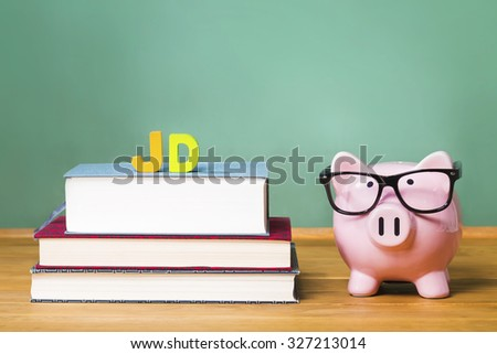 Juris Doctor law degree theme with pink piggy bank with chalkboard in the background as concept image of the costs of education - stock photo