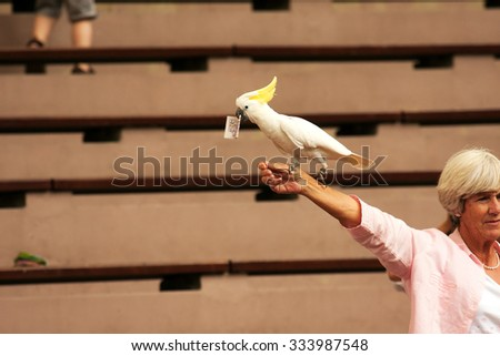 Jurong Bird Park,Singapore-2008.Cockatoo (Cacatuinae) sitting on a woman's hand tourists from Europe and holds in its beak bill 20 dollar, Jurong Bird Park in Singapore in 2008.Editorial. - stock photo