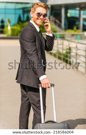 Just arrived. Cheerful young businessman in full suit carrying suitcase and talking on the mobile phone while walking outdoors - stock photo