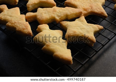 Just baked tree and star shaped Christmas biscuits (cookies), cooling on a black wire rack after removal from oven. Black kitchen worktop below.