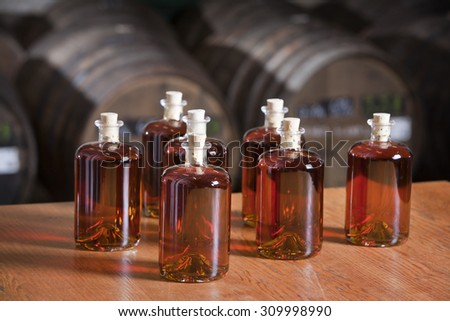 Just bottled liquor with barrels in the background - stock photo