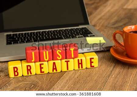 Just Breathe written on a wooden cube in a office desk - stock photo