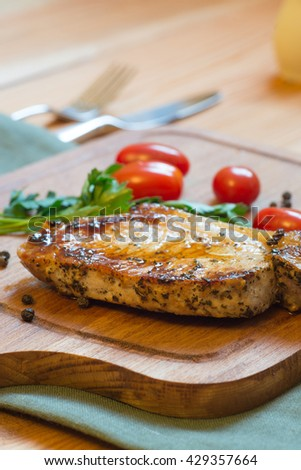 Just cooked grilled pork chop (neck cut) on cutting board.