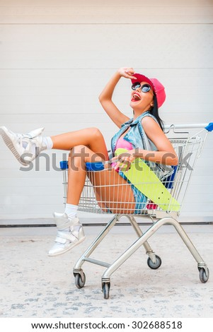 Just for fun. Cheerful young woman adjusting her cap and looking up while sitting in shopping cart against the garage door - stock photo