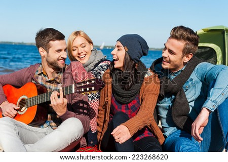 Just friends and guitar. Group of young cheerful people sitting at the riverbank together while young handsome man playing guitar and smiling  - stock photo