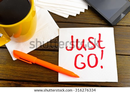 Just go -  handwriting on a napkin with a cup of coffee and phone - stock photo