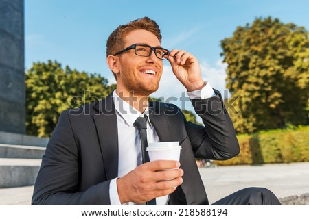 Just inspired. Low angle view of cheerful young man in formalwear holding coffee cup and adjusting his eyeglasses while sitting outdoors - stock photo
