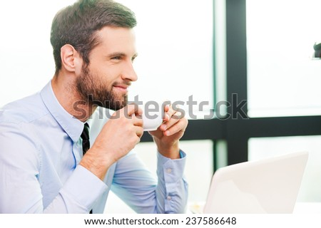 Just inspired. Side view of thoughtful young man in shirt and tie holding coffee cup and looking away while sitting at his working place - stock photo