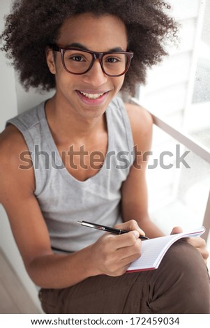 Just inspired. Top view of smiling teenage African boy sitting on the window sill and looking at camera while holding note pad in his hands - stock photo