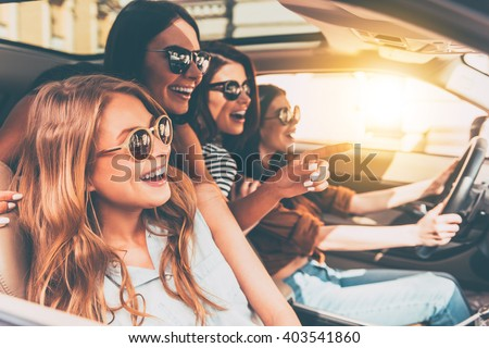 Just keep driving! Side view of four beautiful young cheerful women looking away with smile while sitting in car  - stock photo