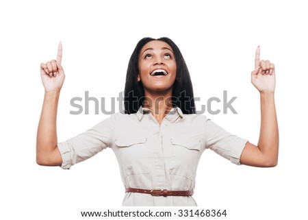 Just look at that! Beautiful young African woman pointing up and smiling while standing against white background - stock photo