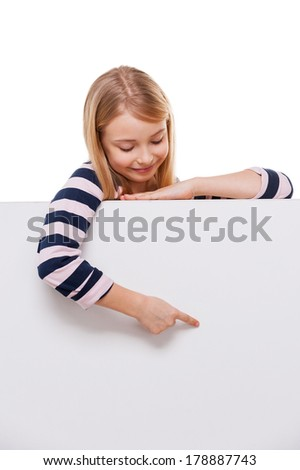 Just look at that! Cheerful little girl leaning at copy space and pointing it while isolated on white