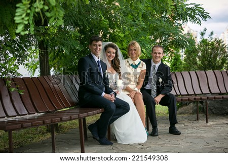 Just married couple and two witnesses sitting on bench at park - stock photo