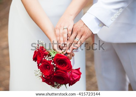 Just married couple compare their wedding rings while holding each others' hands and a bouquet. - stock photo