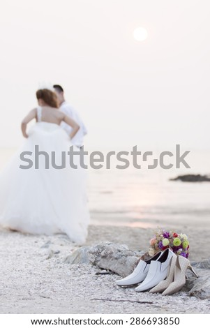 Just married couple holding hands on the beach - stock photo