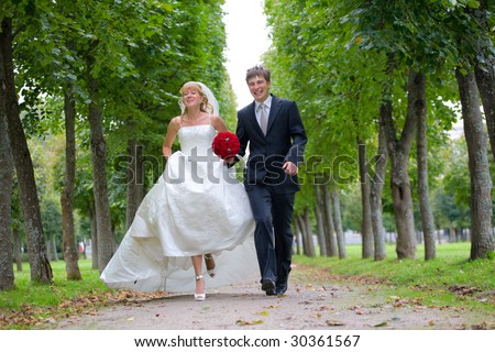 Just married couple is walking fast down the path in the park. They are laughing and the bride is raising a little her gown - stock photo