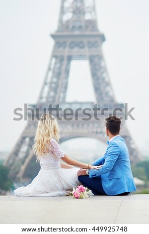 Just married couple near the Eiffel tower on their wedding day. Bride and groom in Paris, France