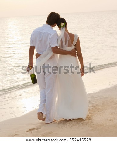 Just married couple on a sandy beach - stock photo
