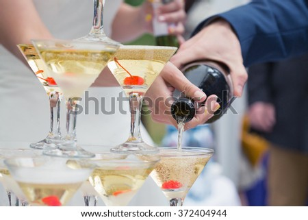 Just married couple pouring sparkling bubbly champagne into glasses - stock photo