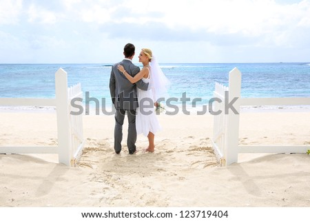 Just married couple standing by a fence towards this ocean - stock photo
