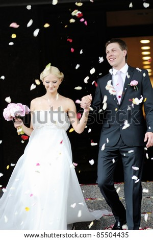 Just married couple under a rain of rose petals - stock photo