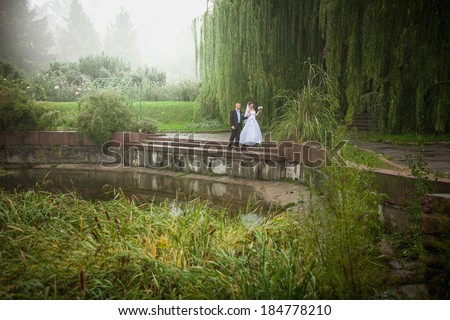 Just married couple walking on riverbank at foggy day - stock photo