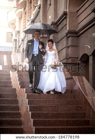 Just married couple walking under umbrella on stairway at rainy weather - stock photo