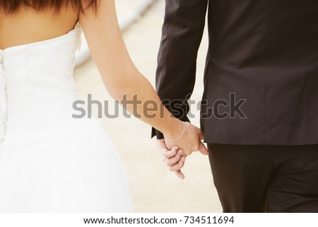 Just married loving couple in wedding and holding hands . Closeup view .