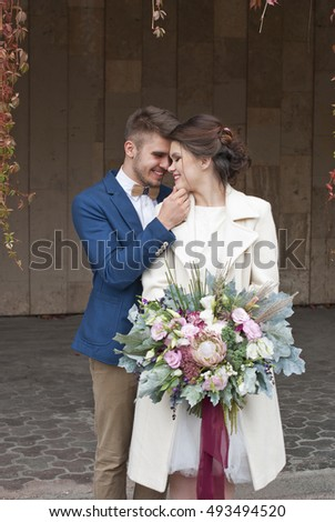 Just married loving couple in wedding dress and suit  outdoor in city setting against wall. Happy bride and groom laughing and kissing. Romantic Married young family.