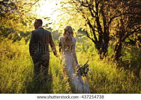 Just married loving hipster couple in wedding dress and suit on green field in a forest at sunset. happy bride and groom walking running and dancing in the summer meadow. Romantic Married young family - stock photo