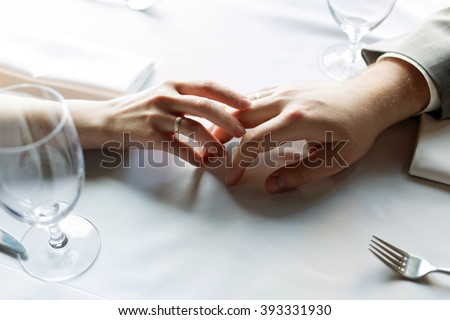 Just married  man and woman with wedding ring holding each other's hands in a restaurant - stock photo