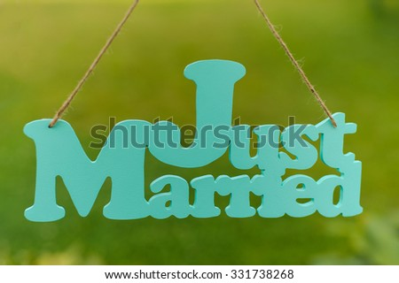 just married wooden sign and wedding rings on the table - stock photo