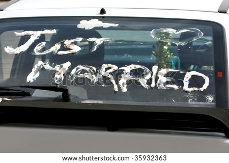 Just married written in foam on the back of a car window - stock photo