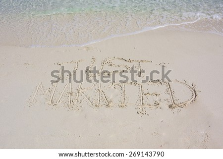 Just married written in sand with the aqua waters of the Caribbean in the background - stock photo