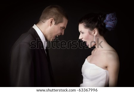 Just married young caucasian couple arguing and shouting at each other, on black background isolated - stock photo