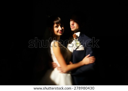 Just married young caucasian couple on black background isolated, a lot of copyspace available - stock photo