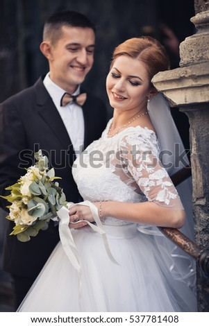 just married - young couple in wedding wear with bouquet of roses