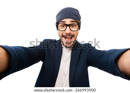 Just me! Cheerful young man in eyewear and hat making selfie while standing against white background - stock photo