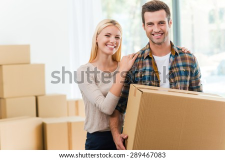 Just moved in. Smiling young man holding a cardboard box while his girlfriend holding hands on his shoulders