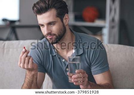 Just one pill can help. Handsome young man holding a glass of water and looking at a pill in his hand while sitting on the couch at home - stock photo